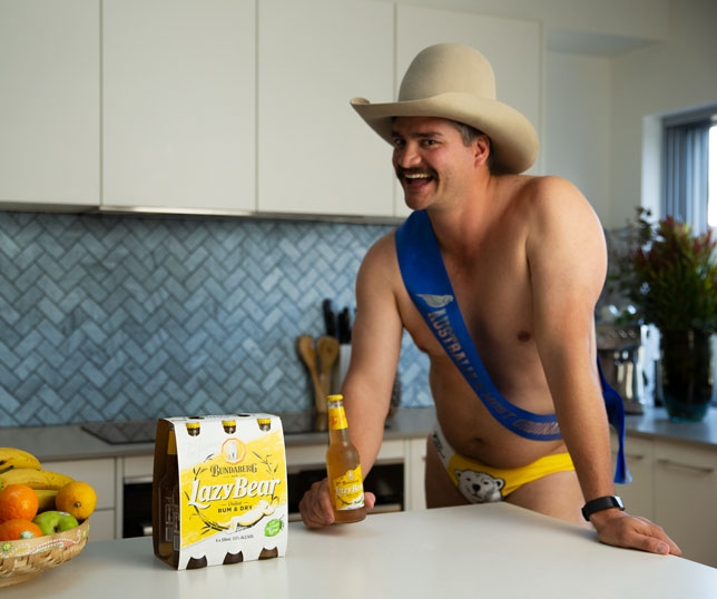 Dingo Dan Leyden holding a bottle of Bundaberg Rum Lazy Bear while wearing a cowboy hat and a pair of Bundaberg Rum Budgy Smugglers inside a kitchen.